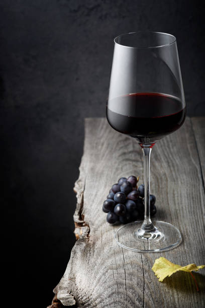A glass of red wine close-up and grapes on an old wooden table stock photo