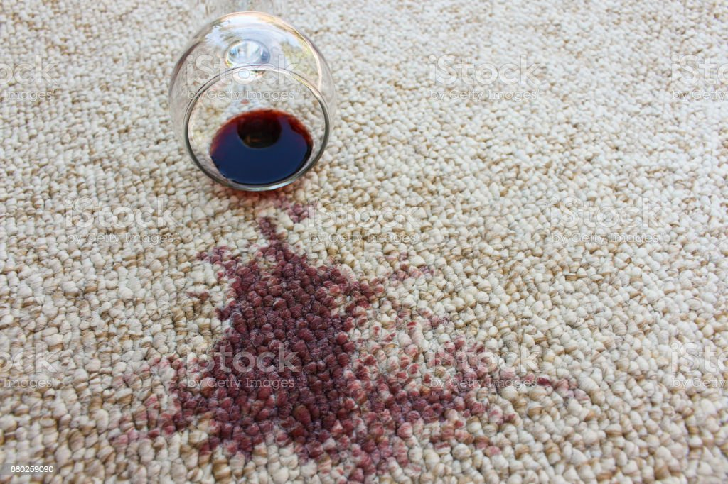 glass of red wine fell on carpet, wine spilled on carpet stock photo