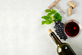 A glass of red wine, grapes and grape leaves wine bottle and corks on the table. Top view with copyspace for your text.