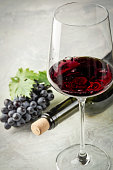 A glass of red wine, grapes and grape leaves wine bottle and corks on the table