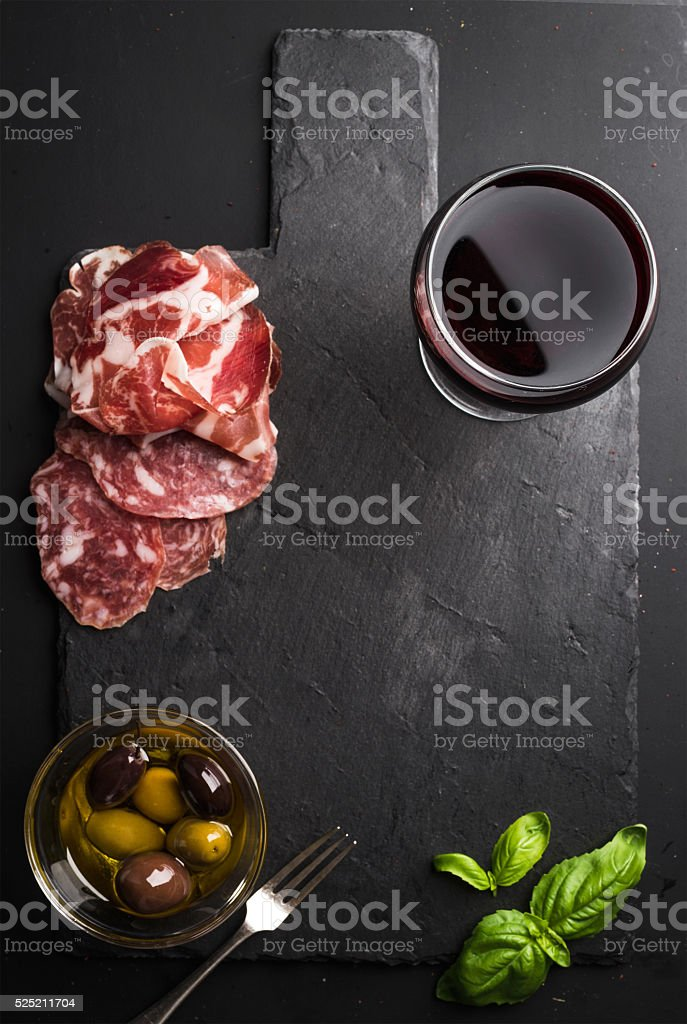 Glass of red wine, meat appetizer, olives and basil on stock photo