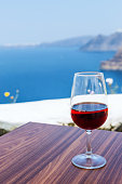 Glass of red wine on a table overlooking a sea