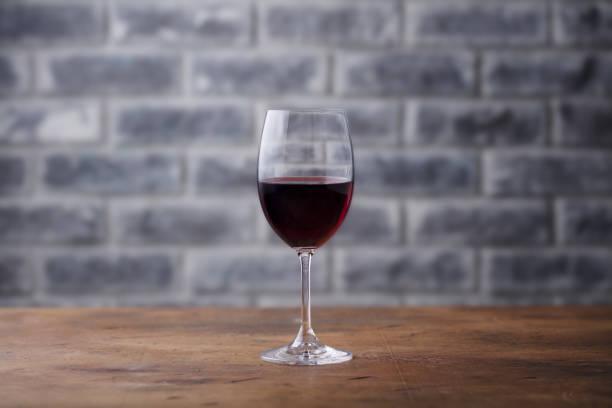 glas rotwein auf steinmauer hintergrund. kopieren sie raum. - italienische speisekarte stock-fotos und bilder