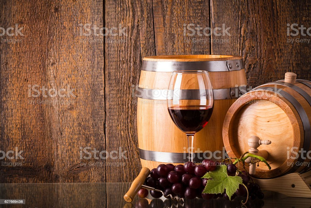 Glass of red wine with barrels and grapes stock photo