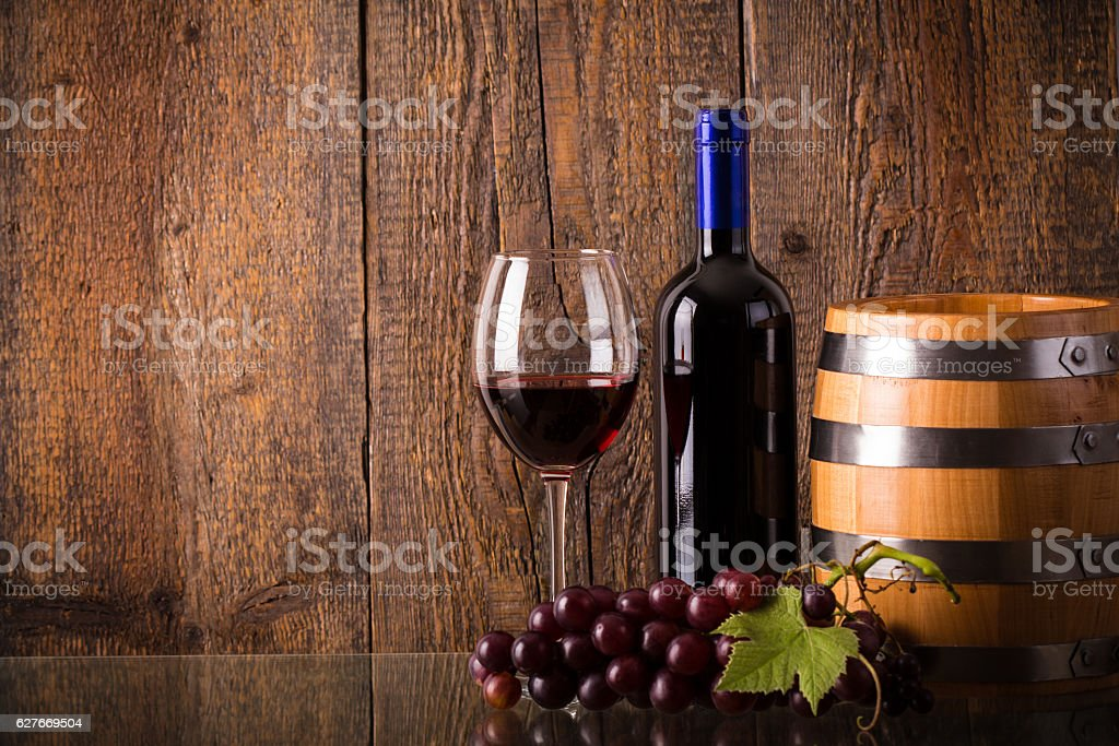 Glass of red wine with bottle barrel grapes on glass stock photo