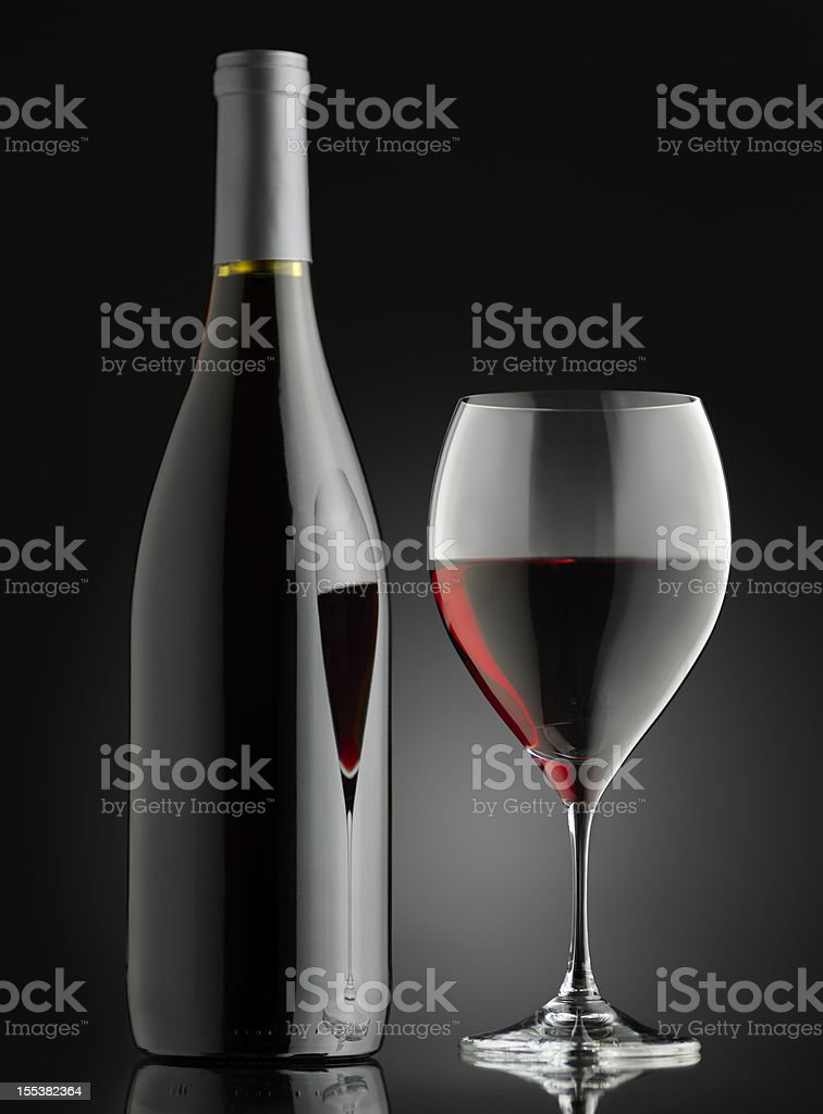 Glass of red wine with bottle on a black background stock photo