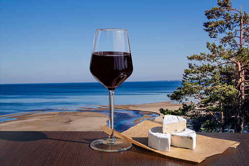 Glass of red wine with brie cheese with view of the White Dune and Baltic see in spring, Latvia. Beach with white sand and blue sea/ocean