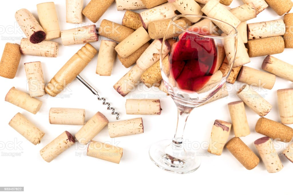 Glass of red wine with corks and corkscrew on a qhite background with copy space stock photo
