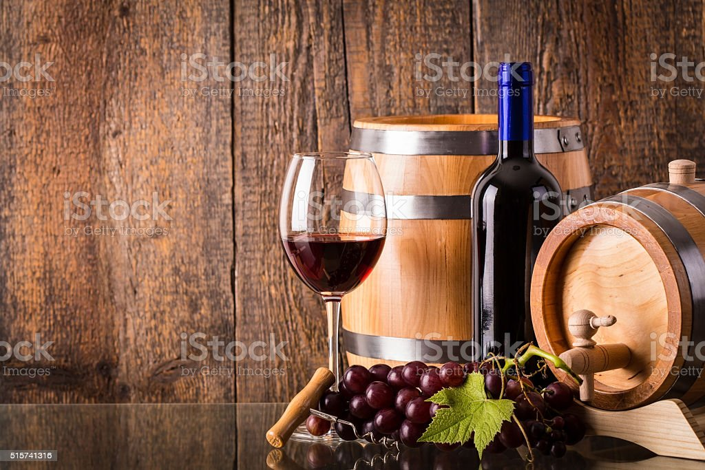 Glass of red wine with dark bottle and barrels stock photo