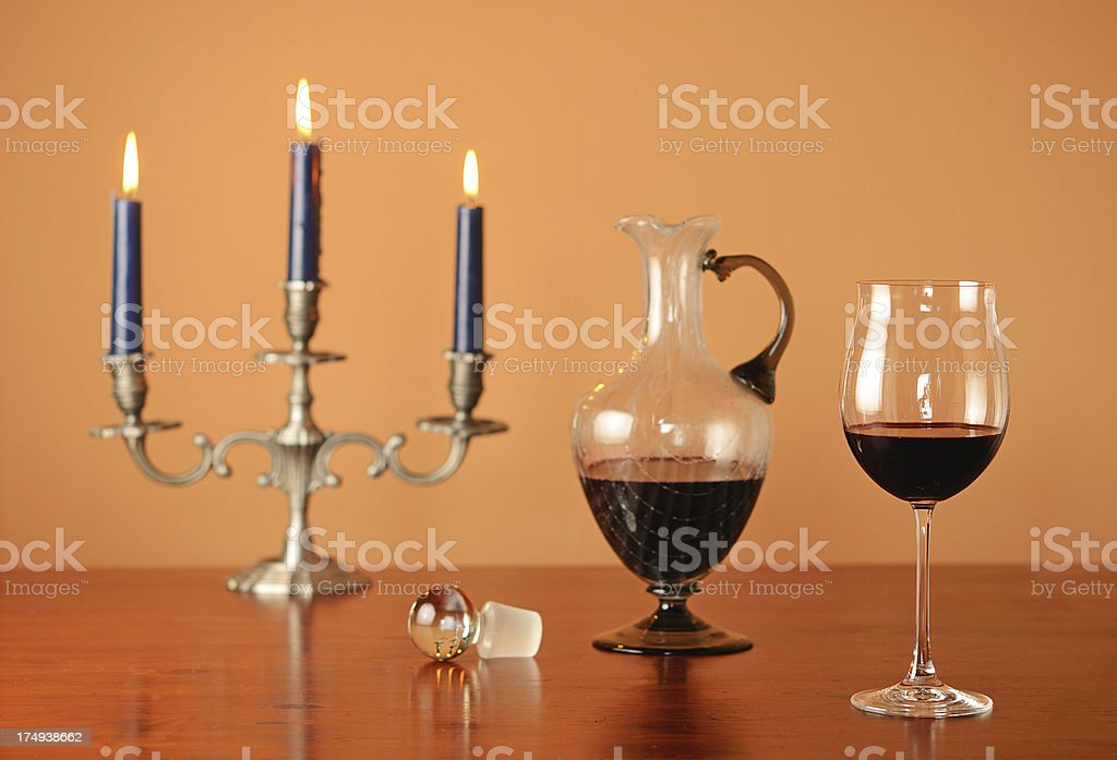 Glass of red wine with decanter and candlestick holder royalty-free stock photo