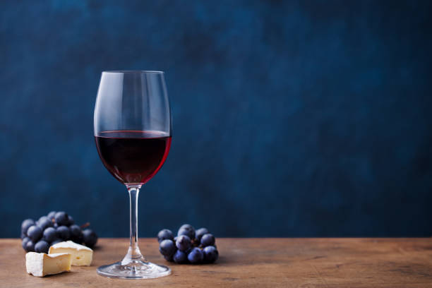 Glass of red wine with fresh grape and cheese on wooden table. Blue background. Copy space. Glass of red wine with fresh grape and cheese on wooden table. Blue background. Copy space merlot grape stock pictures, royalty-free photos & images