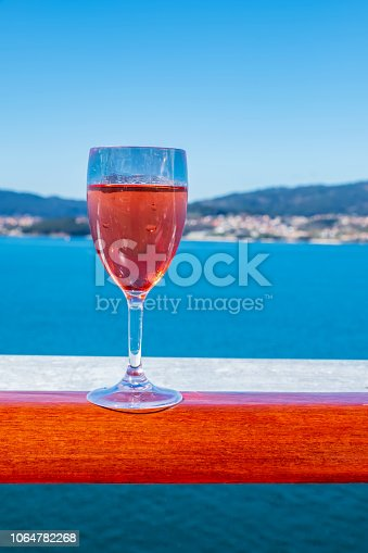 A glass of rose wine on a cruise ship railing, with out of focus background.