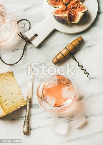 Flat-lay of glass of rose wine with ice cubes, cheese and fresh figs on board over grey marble background. Summer wine and snack set, top view