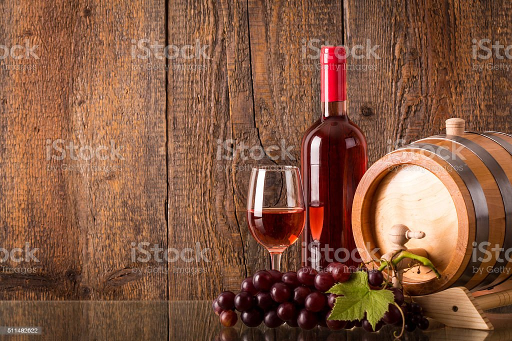Glass of rose wine with bottle barrel grapes stock photo