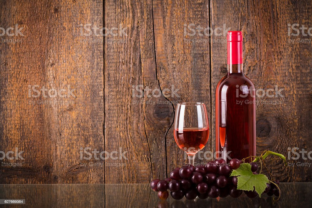 Glass of rose wine with grapes on glass stock photo
