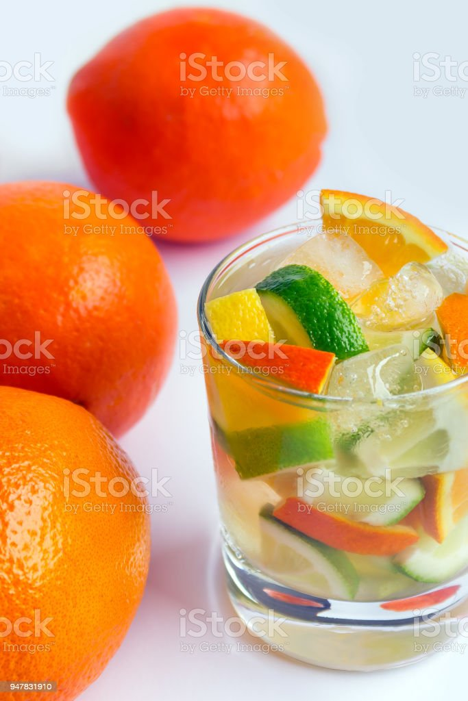 Glass of soda drink with slices of lemon, orange and lime on a white...