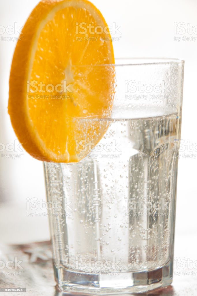 A glass of soda water and a slice of orange. Fresh stock photo