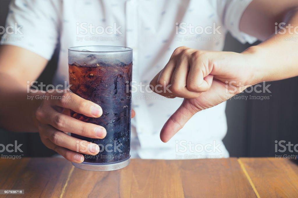 Glas Limonade plantschen mit Eis auf Hand Holztisch Hintergrund, nicht gut schlecht für die Gesundheit-Finger-symbol – Foto