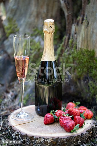 Glass of sparking rose beverage, strawberry  and bottle on moss background