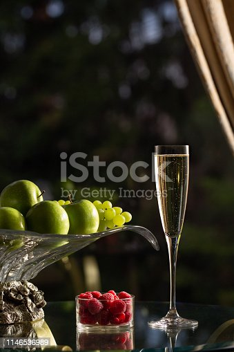 Glass of sparking wine  and vase of fruits