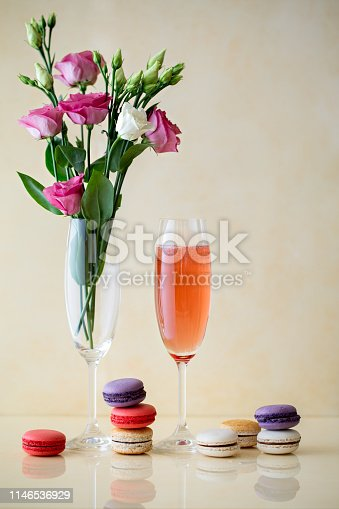 Glass of sparking wine or cocktail, flowers, macaroni