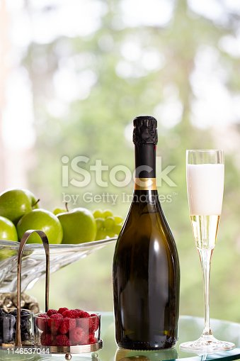 Glass of sparking wine with bottle and vase of fruits
