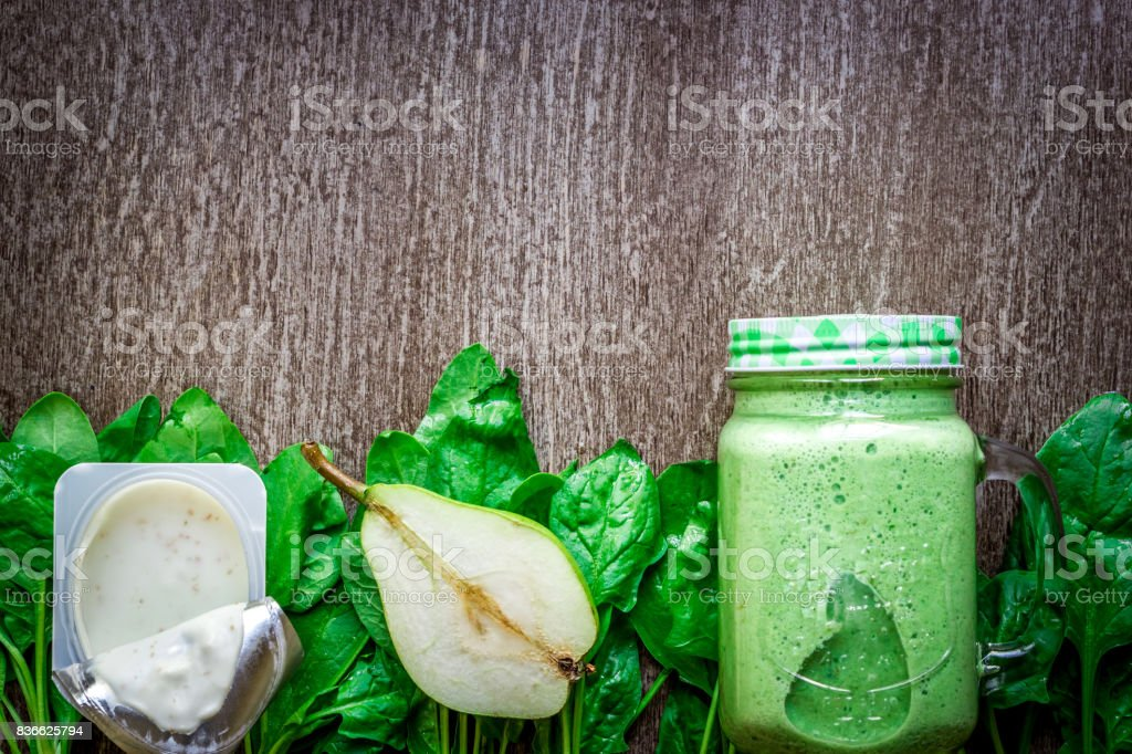 Glass of spinach juice on wooden background stock photo