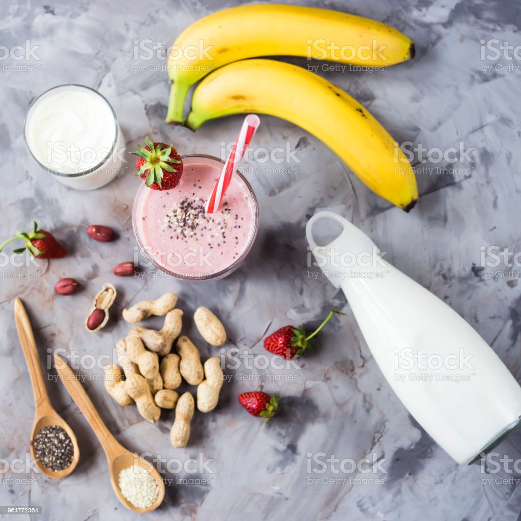 A glass of strawberry banana smoothie among the ingredients for its cooking - strawberries, bananas, milk, yogurt, chia seeds, sesame and peanuts. Healthy eating breakfast. Top view, flat lay royalty-free stock photo