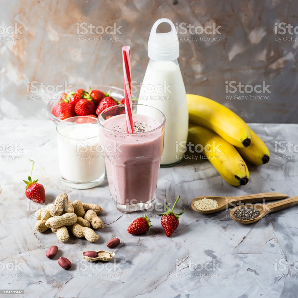 A glass of strawberry-banana smoothie among the ingredients for its preparation. Strawberries, bananas, milk, yogurt, chia seeds, sesame seeds and peanuts. Healthy eating breakfast royalty-free stock photo
