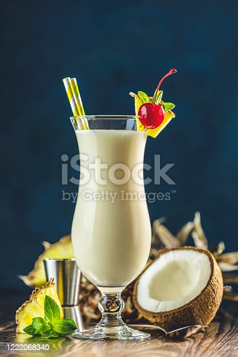 Glass of tasty Frozen Pina Colada Traditional Caribbean cocktail decorated by slice of pineapple and cherry, served on dark wooden background.