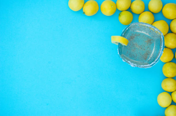 Glass of tasty lemonade with fresh lemons fruits on blue cool background top view copy space stock photo