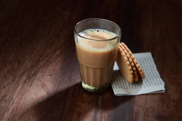 A glass of tea and biscuits on a wooden table. stock photo