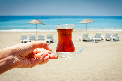Glass of tea in the hands, tea at the beach.