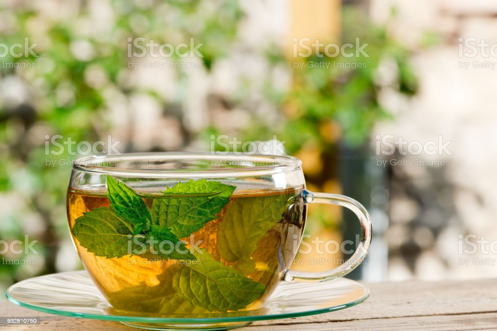Glass of Tea on the Wooden Desk in the Garden stock photo