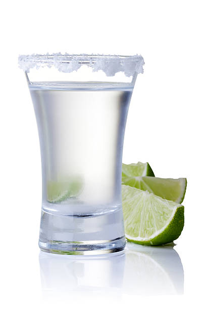 Glass of tequila with lemon on white background shot glass filled with tequila tequila shot stock pictures, royalty-free photos & images