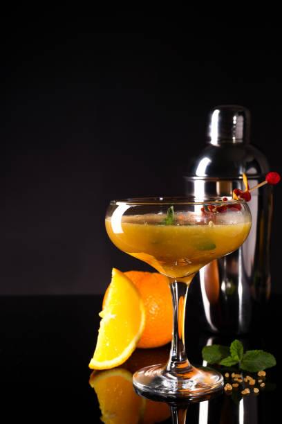 glas des orangefarbenen alkoholischen getränks mit eis und scheiben orangenschale auf dem dunklen hintergrund - dekorierte schnapsflaschen stock-fotos und bilder