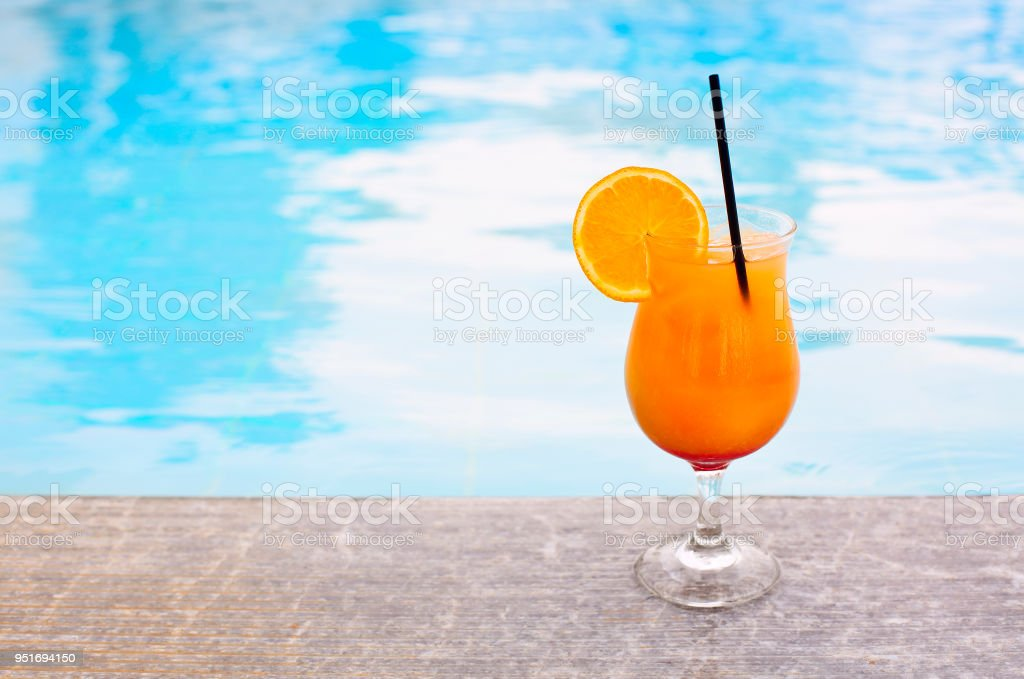 Glass of tropical cocktail on poolside stock photo