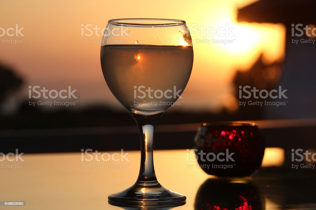 A glass of turkish rakia on a background of sunset - foto stock