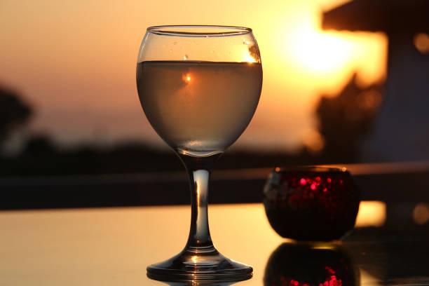 A glass of turkish rakia on a background of sunset - foto stock