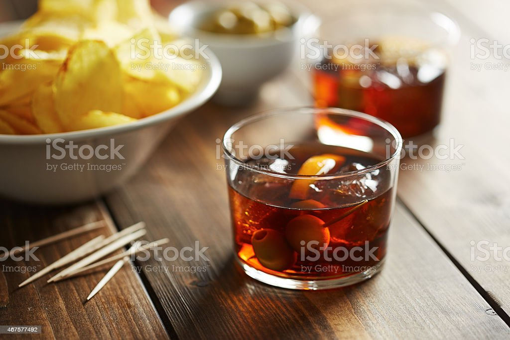 Glass of vermouth with nibbles stock photo