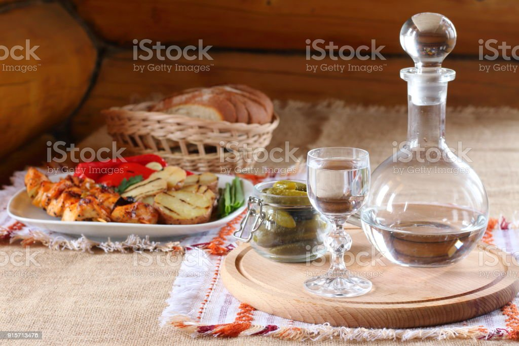 A glass of vodka and a hot snack on the table. stock photo