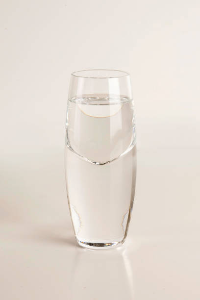 Glass of vodka on light gray background stock photo