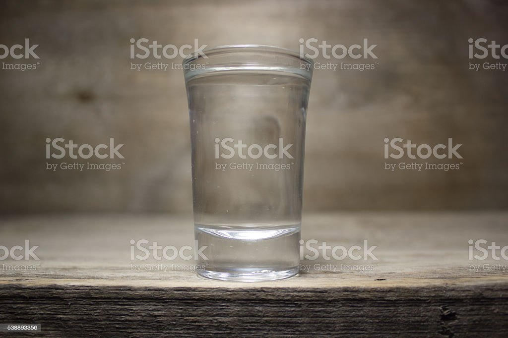 Glass of vodka on wooden table stock photo