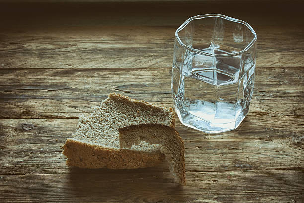 glass of water and hunk black bread – Foto