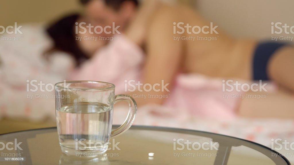 Glas Wasser und auf dem Hintergrund eines Mannes und einer Frau im Bett – Foto