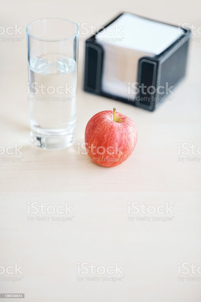 Glass of water, apple and note paper stack royalty-free stock photo