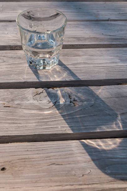 Glass of water casting shadow on wooden table – zdjęcie