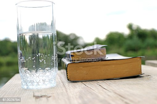 845307398 istock photo glass of water  close to the book, the Bible 612029754