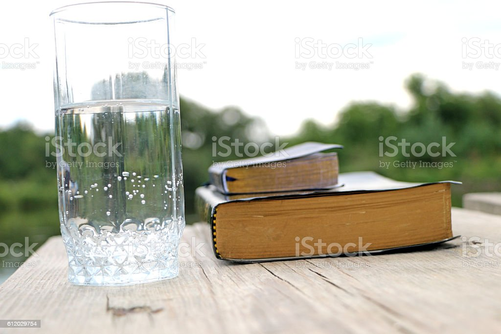 glass of water  close to the book, the Bible stock photo
