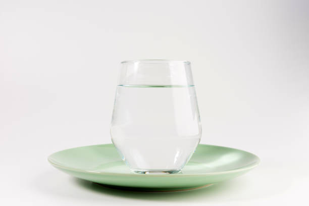 glass of water in a plate isolated on white background stock photo